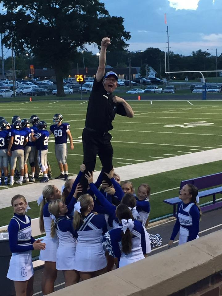 Father Mike Baldwin shows his spirit by stunting and cheering with the St. Mary's Colgan cheer squad during the Panthers' 34-24 home win over Baxter Springs. (Photo courtesy of Jess Nicholson)