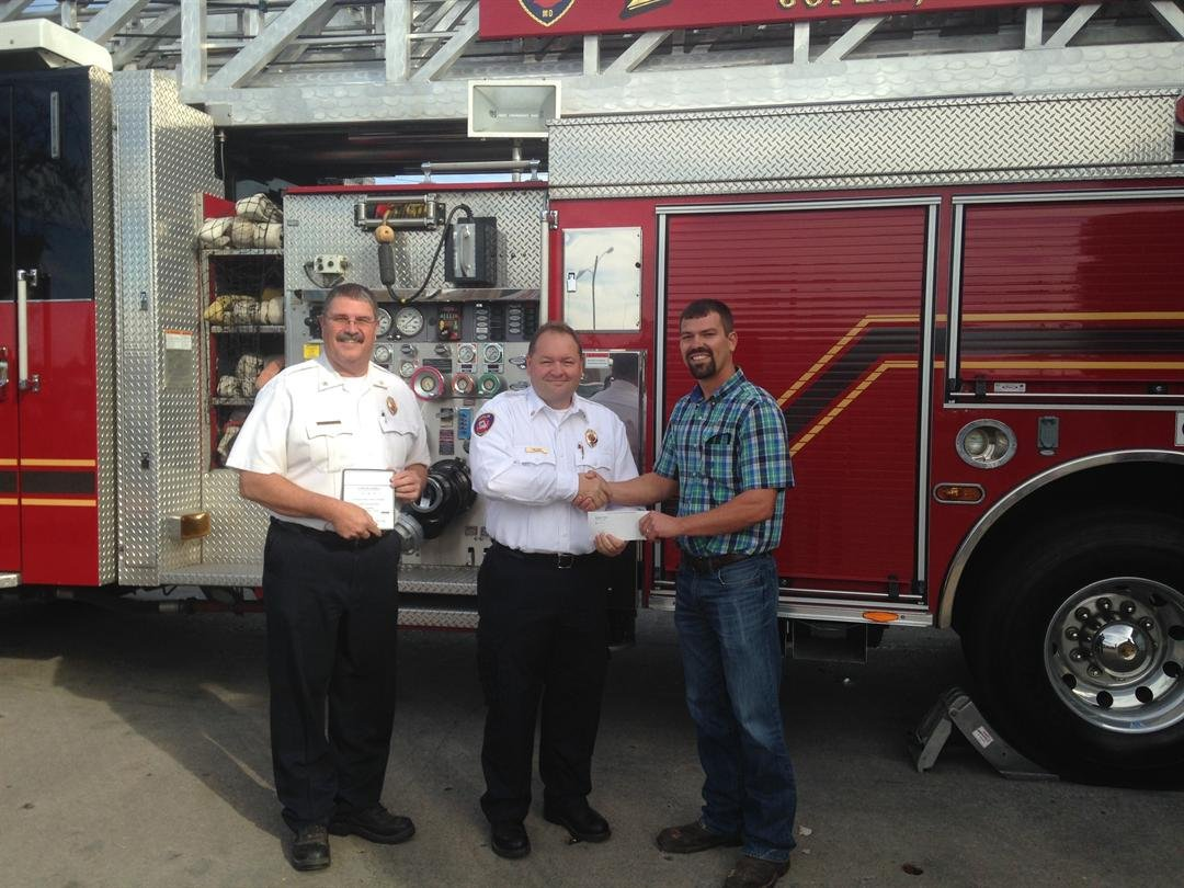 Fire Marshall Dale Brooks, Chief Jim Furgerson and Missouri American Water Interim Operations Manager, Jeremy Boes presenting the check. (Photo Courtesy of MO American Water)
