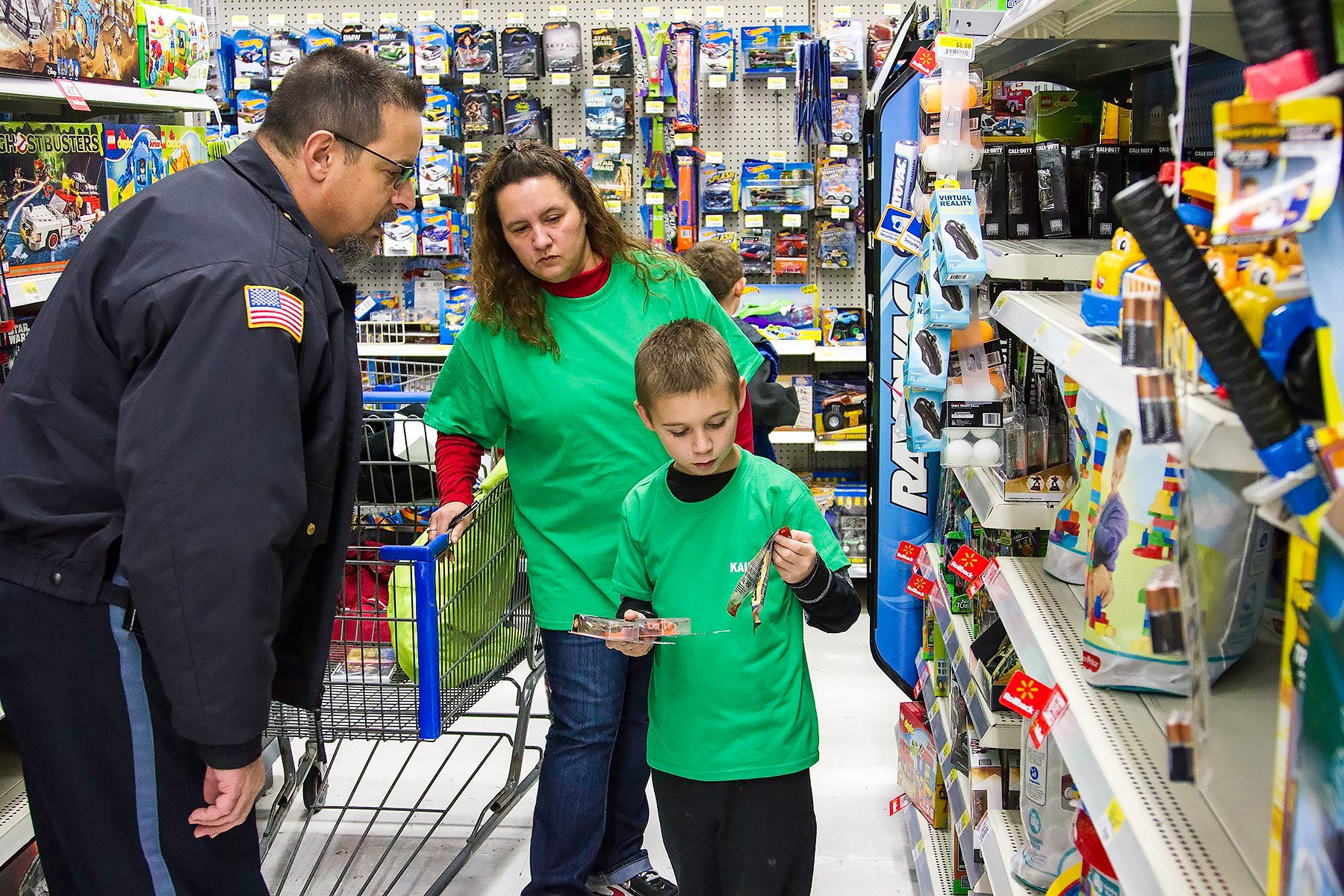 Officer Philip Brice, Kristy Howard, and Kaiden Osborne shop for gifts.