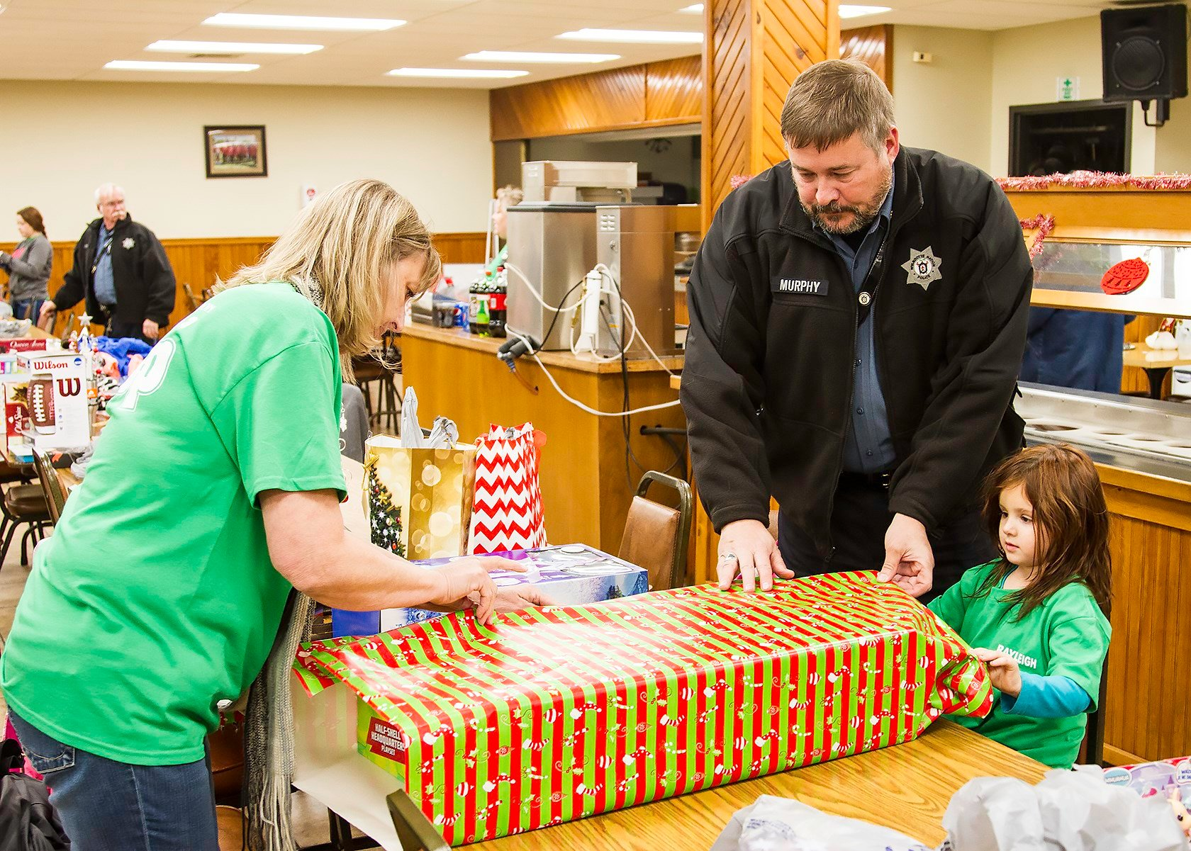 Janette Arnold, Police Chief Ken Murphy, and Rayleigh Barfell wrap presents.