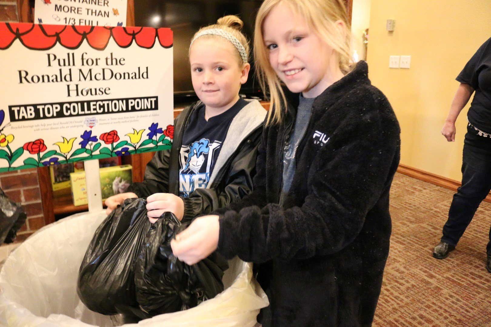Southeast 4th graders Dahlia DeVault (front) and Samantha Dietz dump their tabs into the collection bin at Ronald McDonald House in Joplin.