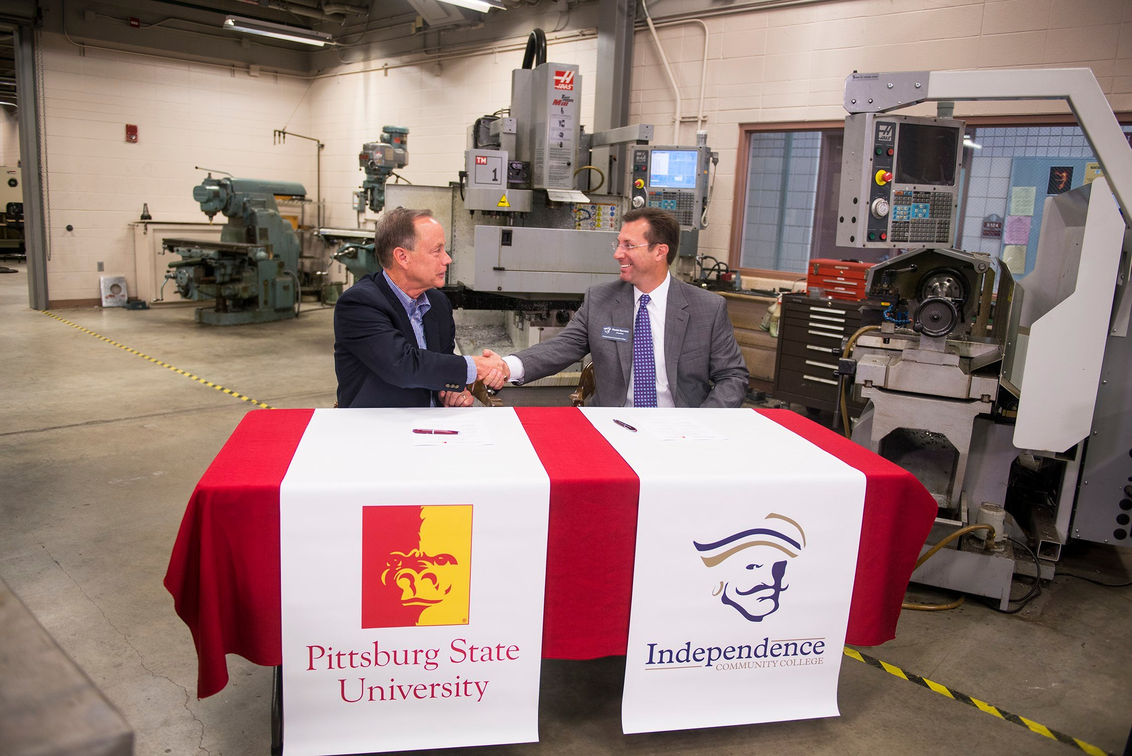 Steve Scott, president of Pittsburg State University, and Daniel Barwick, president of Independence Community College, seal the signing of an articulation agreement with a handshake on Tuesday morning at the Kansas Technology Center.