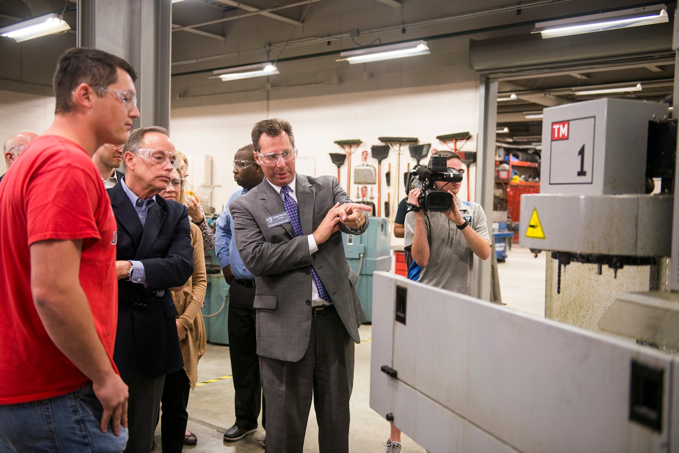 Daniel Barwick (right), president of Independence Community College, and Steve Scott, president of Pittsburg State University, discuss elements of a CNC machine with Eric Bradshaw (left), a senior from Independence, Kansas, at the Kansas Technology Center