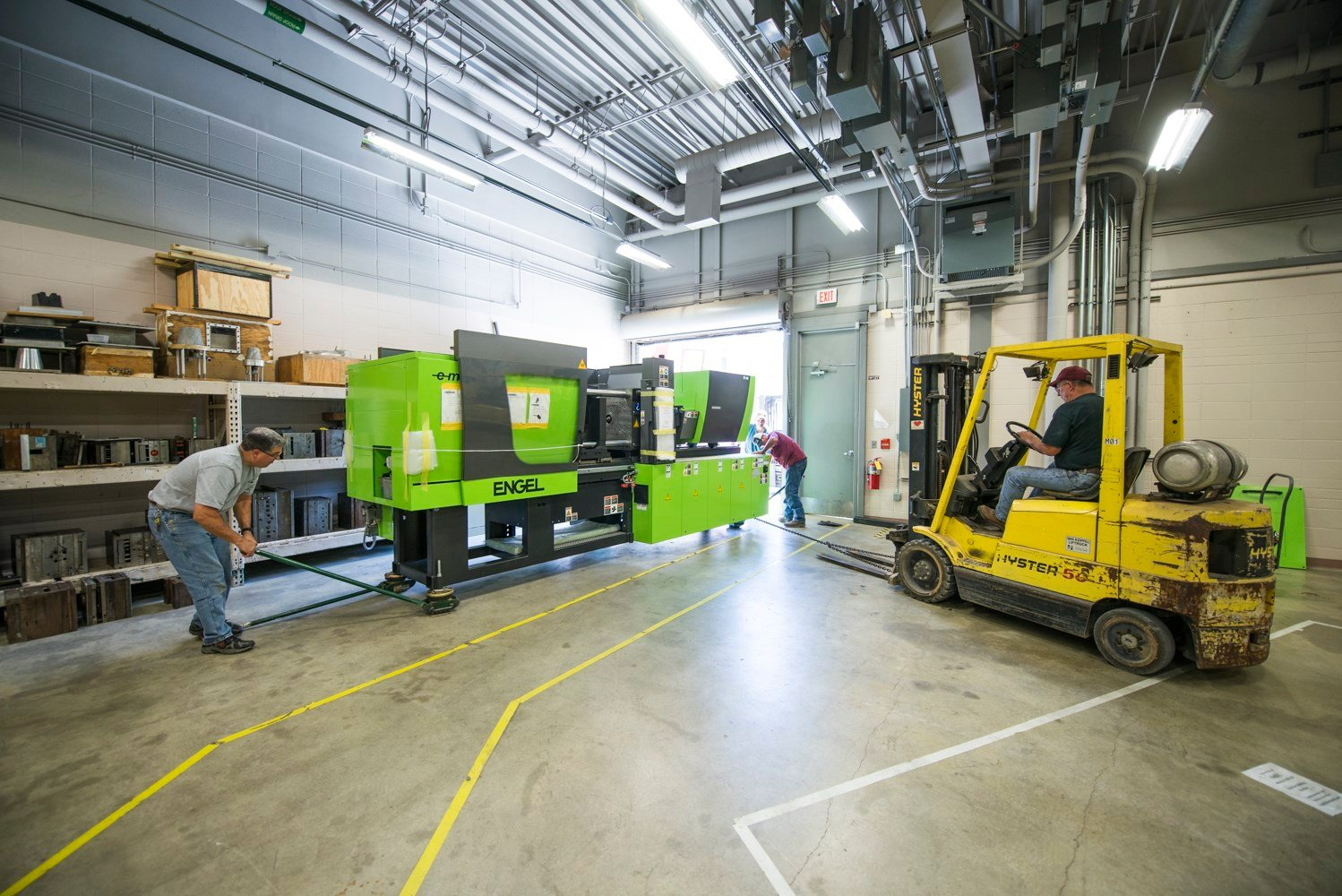 Workers at Pittsburg State take possession of an injection molding machine from Engel. Pittsburg State Plastics Engineering Technology students will use the machine and its next generation controls in their coursework.