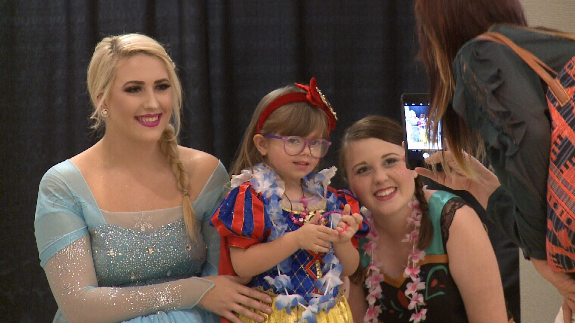 Little princess gets her picture taken with big princesses.