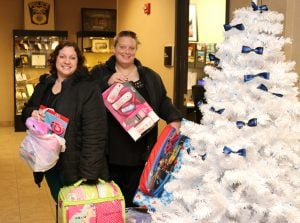 Child advocates Charleen Workman and Katie Douglas with the stocking stuffers.