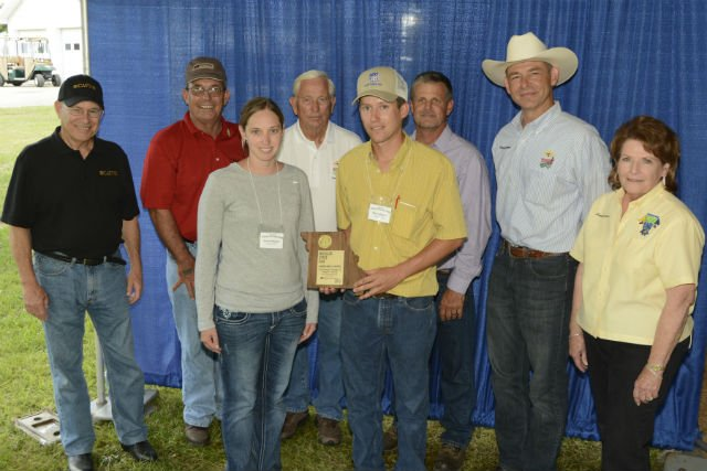 Shown in the picture behind the farm family is (from left to right) Dr. Tom Payne, Vice Chancellor and Dean, University of Missouri, College of Agriculture, Food and Natural Resources; Blake Hurst, President, Missouri Farm Bureau; Lowell Mohler, Missouri