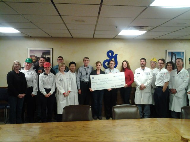 PHOTO:  General Mills–Joplin Plant Manager Carolyn Mendel, Community Action Council Chair Tabitha Morris (in red) and several General Mills employees present OFH President/CEO Bart Brown and OFH Board Member Gary Naab with a $10,000 donation...