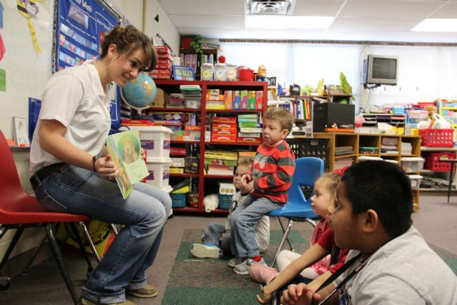 Kelsey Matthews, NEO sophomore, is reading to Ms. Traci Eden's kindergarten class at Washington Elementary.  Elementary students pictured from left to right include: Maddox Mercer, Ryder Oakley, Holly Christman, Ethan Weaver and Arkis Sikara.