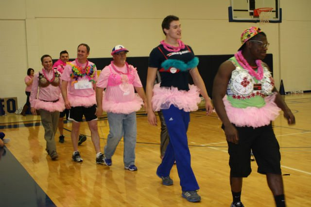 """NEO athletes and coaches modeling bras during NEO's """"Shoot for the Cure"""" event"""