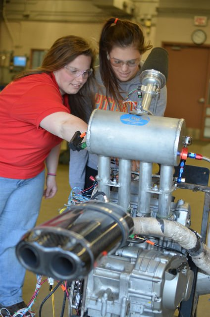 PSU students Jennifer Bradley (left) and Rachel Meyer, work on a Formula-style race engine inside the Kansas Technology Center. Bradley is a senior from Lancaster, Pa., and Meyer is a freshman from Spring Hill, Kan.