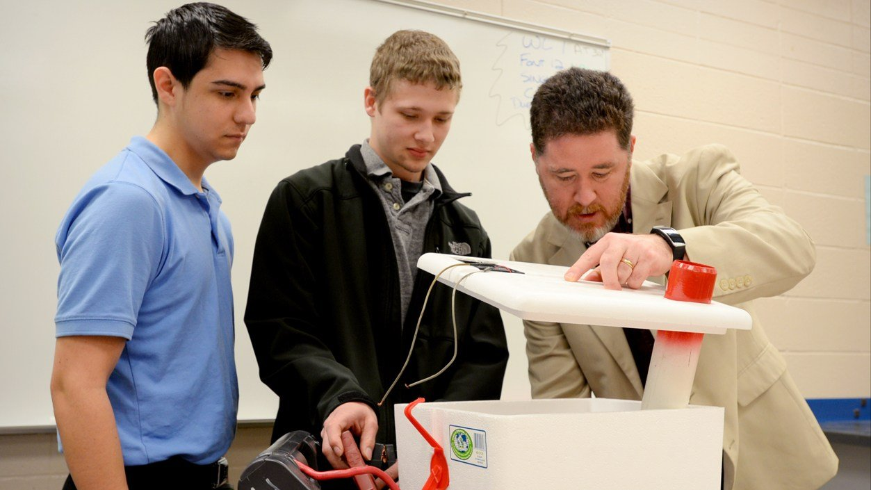Associate Professor Scott Norman, right, inspects a portable AC unit developed by students Daniel Torres, left, and Zack Sutton in his automotive climate control systems course.