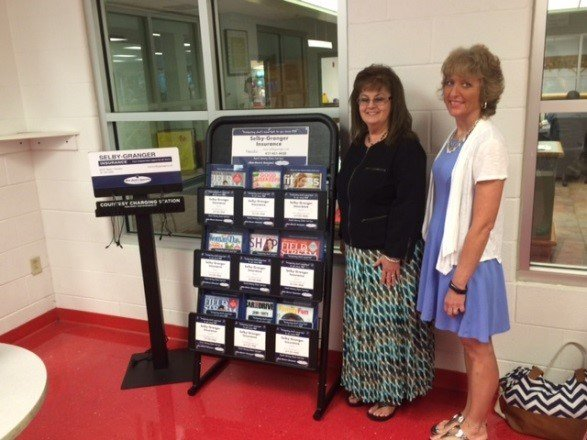 Beverly Granger (L), owner of Selby-Granger Insurance and Jana Fornelli (R), branch executive director of the Neosho Freeman Family YMCA pose with the electronic charging station and magazine gift service donated to the YMCA by Selby-Granger Insurance, Ne