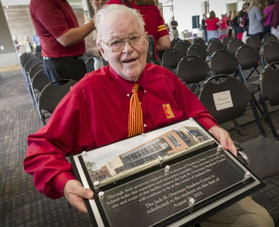 Jack Overman, for whom PSU's Overman Student Center is named, poses with the plaque to be installed in the student center's expansion.