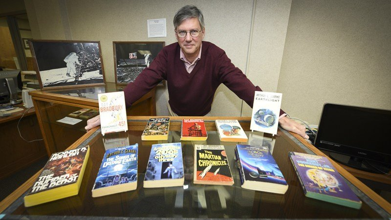 : Steve Cox, curator of special collections and university archives at PSU's Leonard H. Axe Library, shows some of the library's collections dealing with science fiction and space exploration.